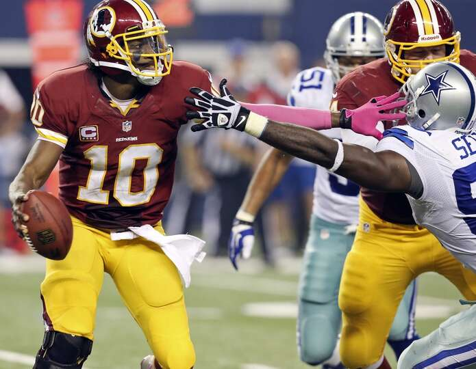 Washington Redskins' Robert Griffin III looks for room under pressure from Dallas Cowboys' George Se