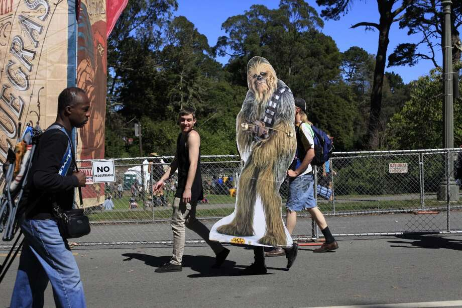 With the help of his roommates, ChewbaccaSF and Scott Renner move between stages at Hardly Strictly Bluegrass in San Francisco, Calf. Photo: Mike Kepka, The Chronicle