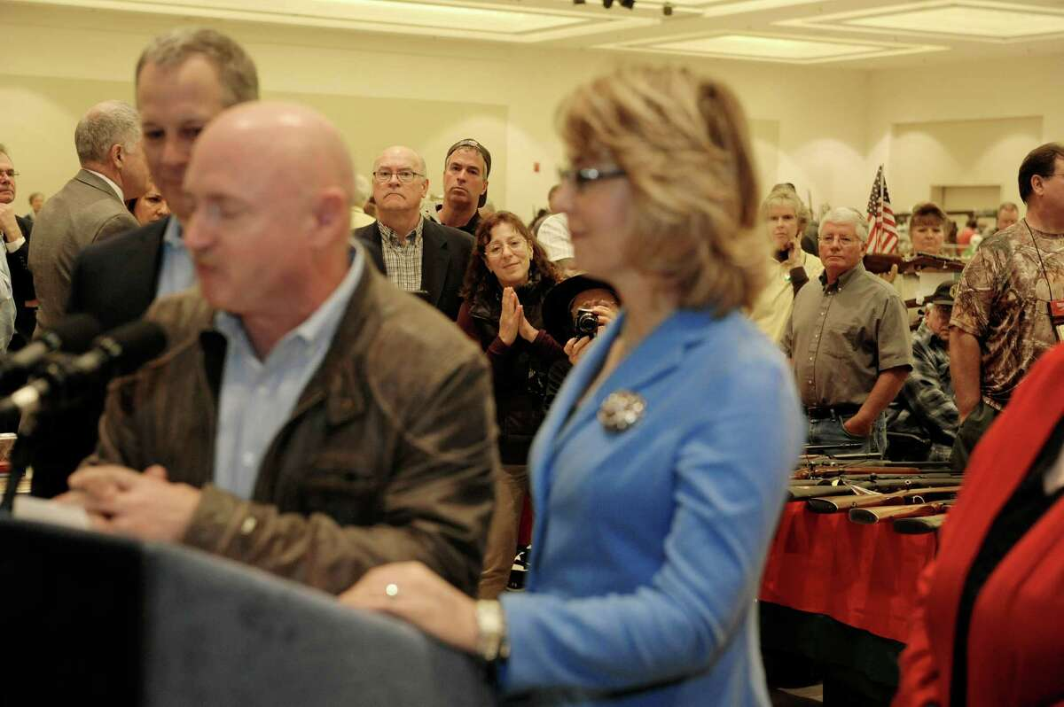 People look on as Mark Kelly, foreground left, and his wife Former U.S. Rep. Gabby Giffords, foreground right, address the media at the Saratoga Springs Arms Fair on Sunday, Oct. 13, 2013 in Saratoga Springs, NY. (Paul Buckowski / Times Union)