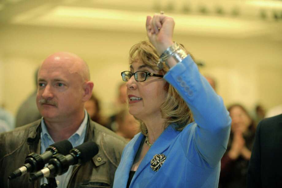 Mark Kelly, left, and his wife, Former U.S. Rep. Gabby Giffords, right, address the media during a press conference at the Saratoga Springs Arms Fair on Sunday, Oct. 13, 2013 in Saratoga Springs, NY.       (Paul Buckowski / Times Union) Photo: Paul Buckowski / 00024253A