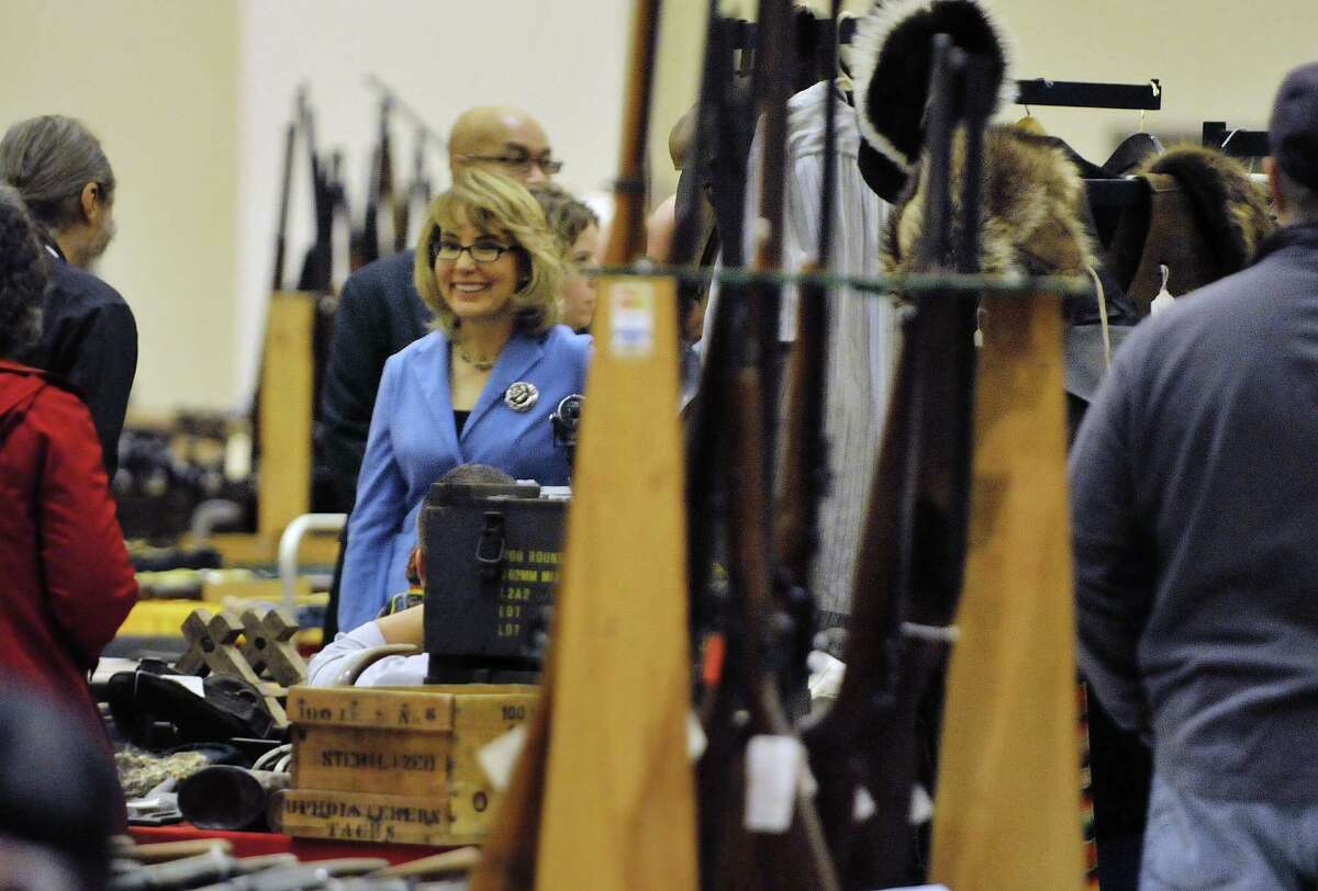 Former U.S. Rep. Gabby Giffords, center, visits with gun dealers at the Saratoga Springs Arms Fair on Sunday, Oct. 13, 2013 in Saratoga Springs, NY. (Paul Buckowski / Times Union)