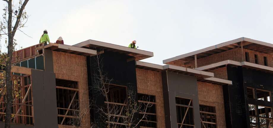 Workers construct multifamily units in the Springwoods Village master-planned community adjacent to the Exxon Mobil campus, in Spring, Texas. Photo: Billy Smith II, Chronicle