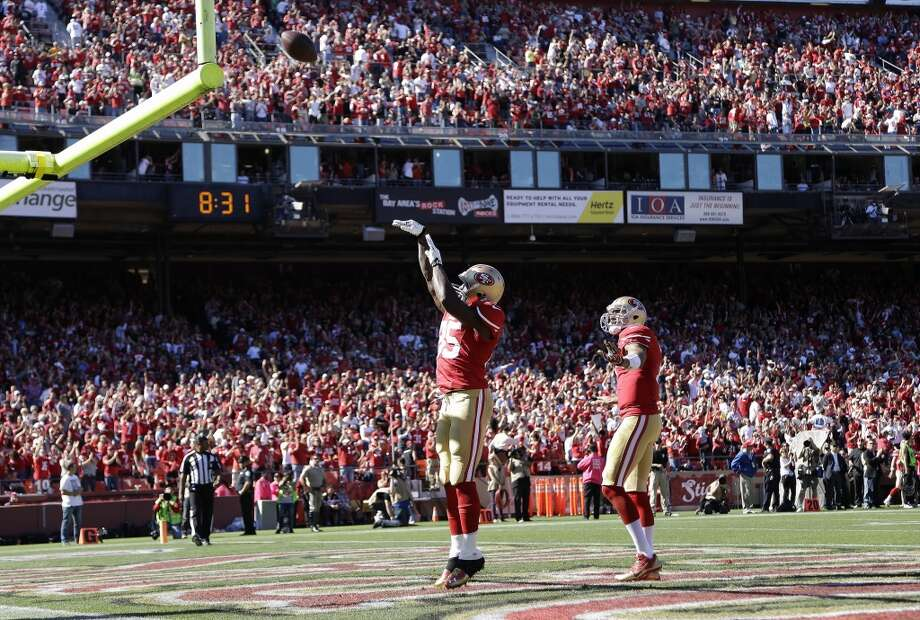 San Francisco 49ers tight end Vernon Davis (85) shoots the ball over the goal post after scoring on a 61-yard touchdown reception from quarterback Colin Kaepernick, right, during the second quarter of an NFL football game against the Arizona Cardinals in San Francisco, Sunday, Oct. 13, 2013. Photo: Ben Margot, Associated Press
