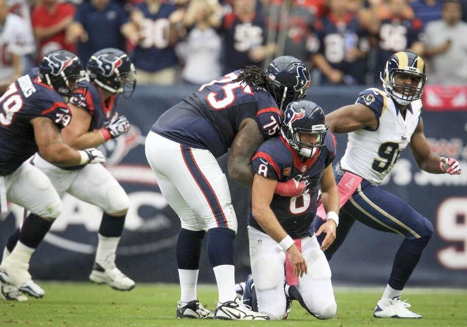 Texans quarterback Matt Schaub gets a hand up from the turf from tackle Derek Newton. Photo: Karen Warren, Houston Chronicle