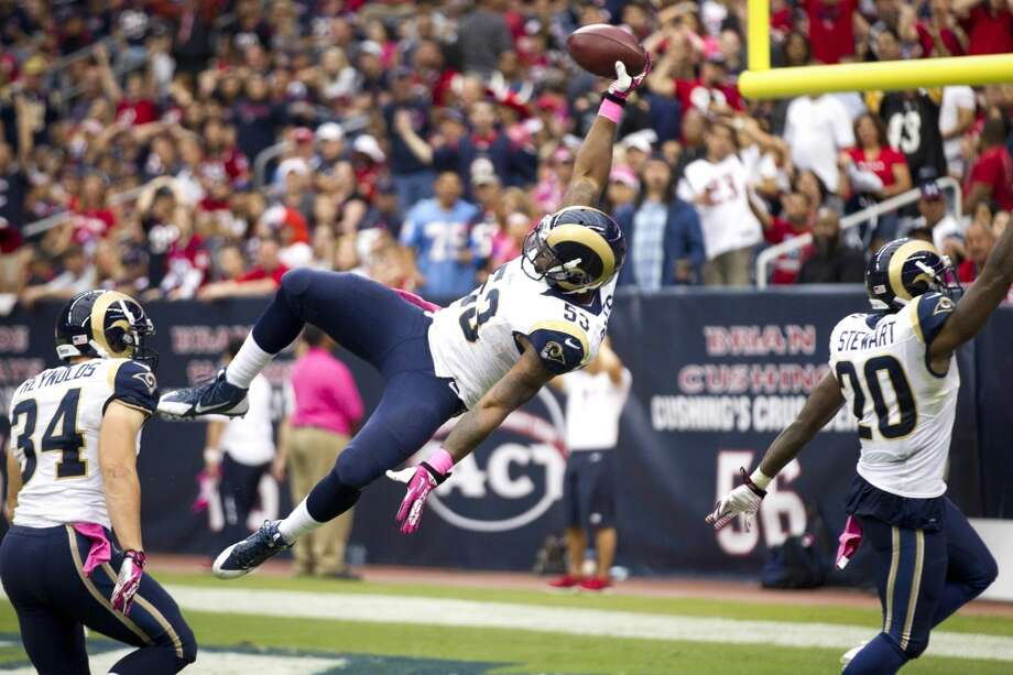 Rams linebacker Daren Bates leaps into the end zone as he returns a fumble by Texans kick returner Keshawn Martin for a touchdown during the third quarter. Photo: Brett Coomer, Houston Chronicle