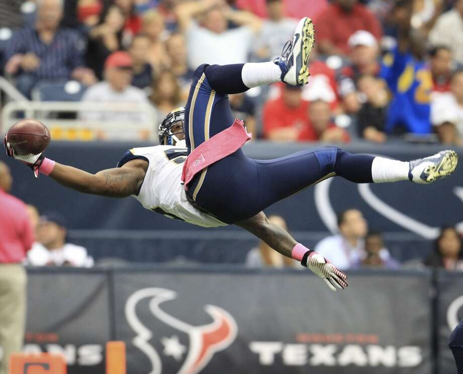 Rams linebacker Daren Bates  flips into the end zone as he returns a fumble by Keshawn Martin for a touchdown. Photo: Karen Warren, Houston Chronicle