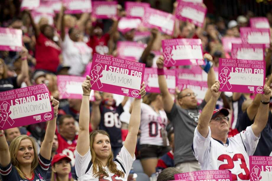 Texans fans hold up signs in support of breast cancer survivors during the second quarter. Photo: Brett Coomer, Houston Chronicle