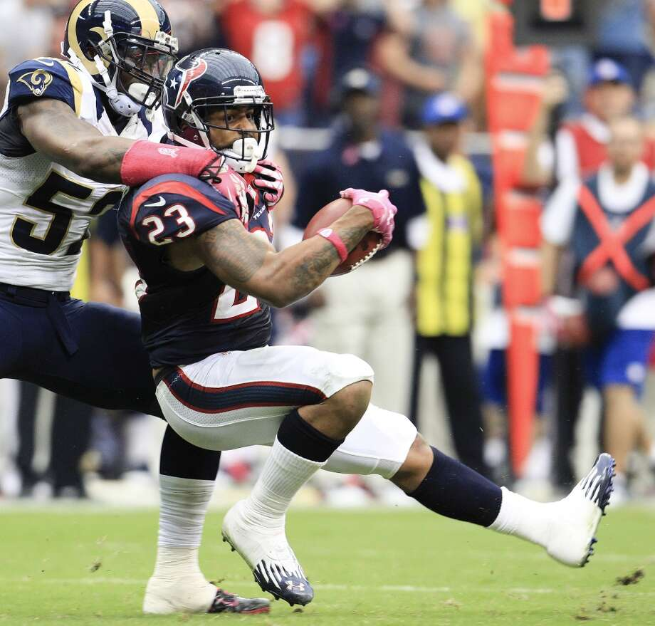 Texans running back Arian Foster is tackled by Rams linebacker Alec Ogletree. Photo: Karen Warren, Houston Chronicle