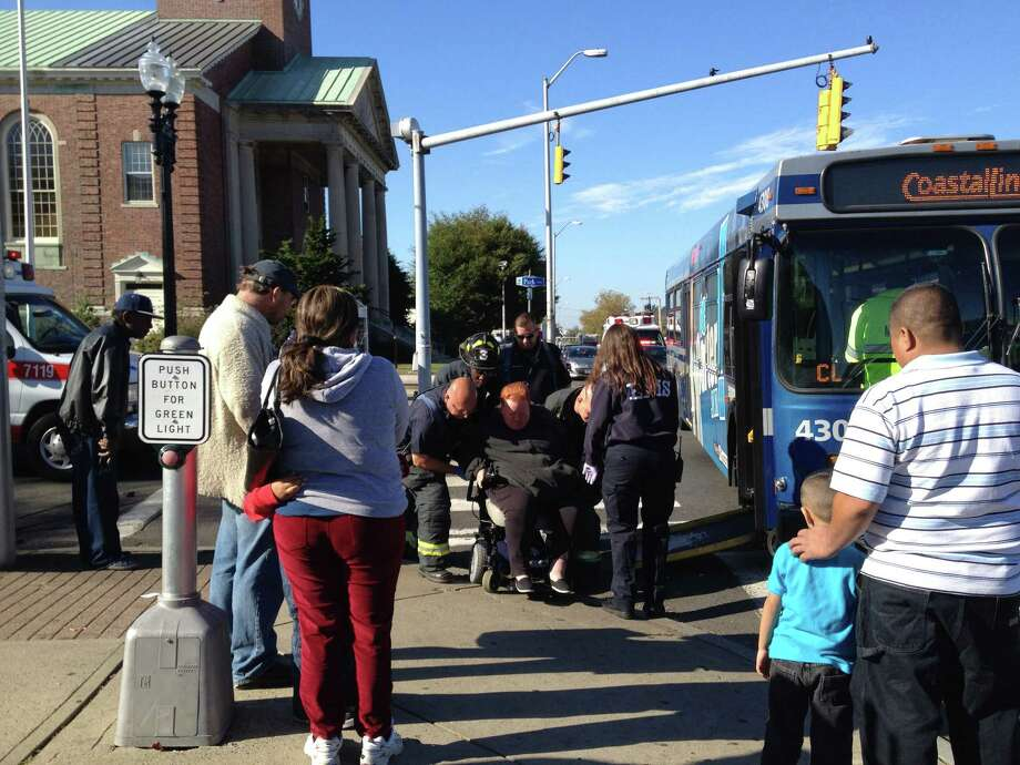 Four people were injured when a public transit bus and a car collided in downtown Bridgeport on Monday morning. Photo: Frank Juliano / Connecticut Post
