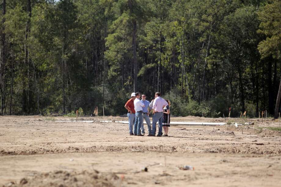 Contractors walk a site Wednesday October 9, 2013 were they will build single family homes in the Springwoods Village master-planned community adjacent to the Exxon Mobil campus, in Spring, Texas. (Billy Smith/Chronicle) Photo: Billy Smith II, Chronicle