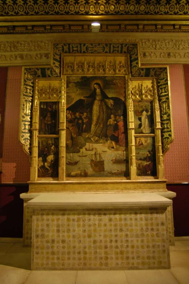 "The painting over the altar in chapel inside the Alcazar's La Casa de Contrataci—n is ""Our Lady of Navigators,"" which shows a group of famous explorers, including Columbus, and is said to be the first painting that represents the European discovery of the New World. Photo: Spud Hilton, The Chronicle"