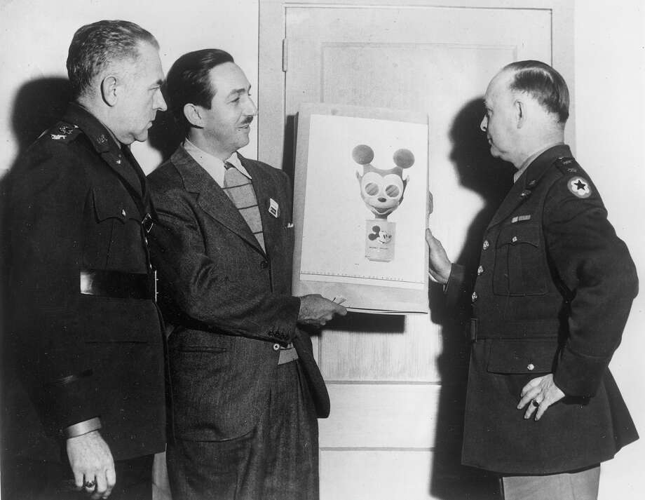 Above: Animator Walt Disney, second from left, hands over his sketch of a Mickey Mouse gas mask to Maj. Gen. William Porter, right, in Washington, D.C. in 1942.  Civilian defense and chemical warfare officers planed to produce the design intended to encourage children to use masks for protection during World War II. Photo: ASSOCIATED PRESS / AP1942