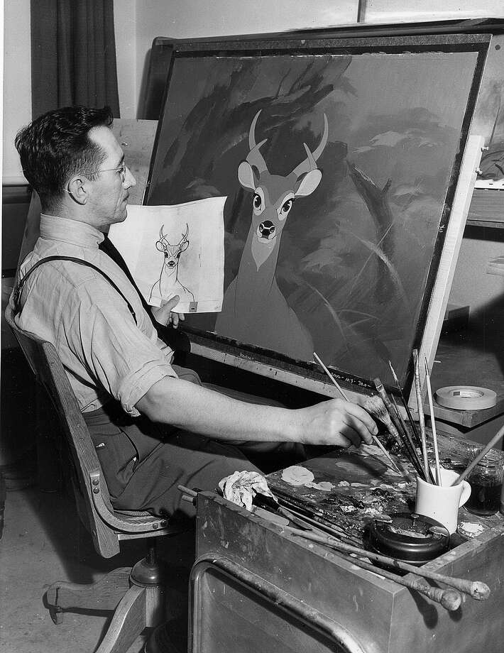 "Each of the hundreds of backgrounds in the Bambi film was painstakingly done in oils, as shown in 1942, in Los Angeles. Thus, a forest for the action in which the story takes place was created with actual depths, not just a ""background."" Above, background artist Richard Anthony checks a sketch of grown-up Bambi against one of these colorful and realistic forest settings. Photo: ASSOCIATED PRESS / AP1942"