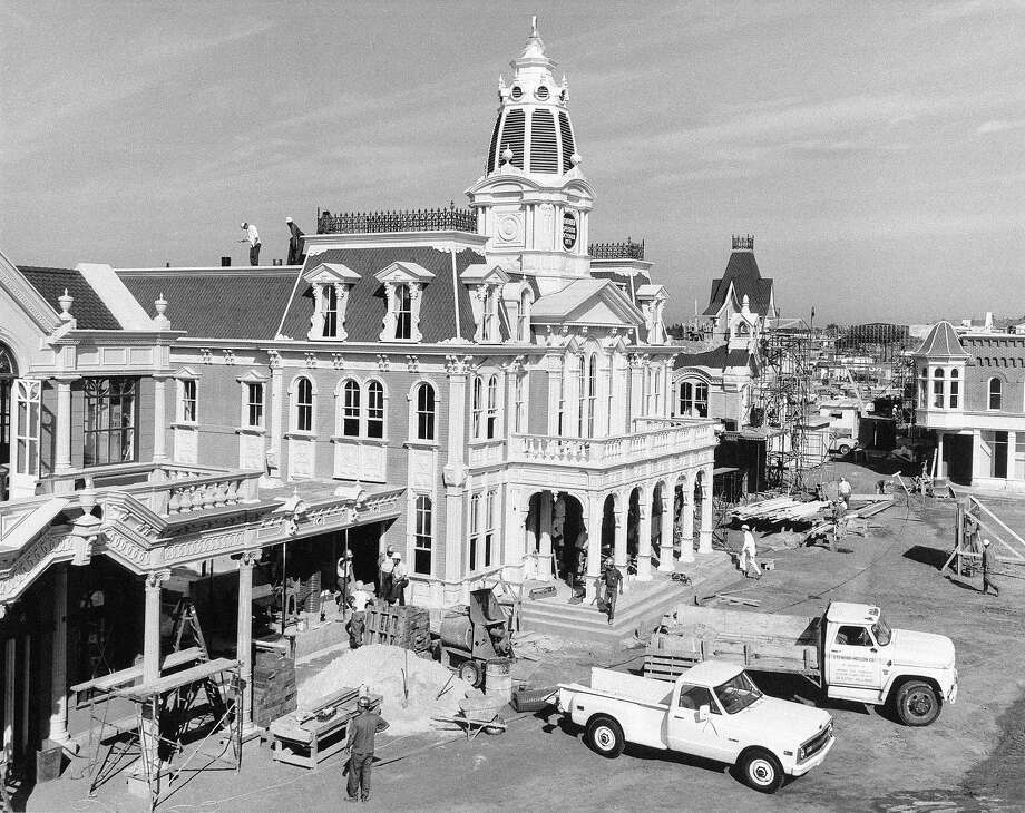"Above: Workmen bustle about Town Hall in the Main Street U.S.A. area of Walt Disney World's ""Magic Kingdom"" theme park in Florida, Nov. 1970, closest to completion out of six major lands. Main Street depicts Americana, circa 1890-1910, with quaint shops of the period, a grand Victorian railroad station for the Kingdom's steam-engined railroad line, horse-drawn street cars, and, in an elegant old-world hotel setting, a variety of information services for visitors to Walt Disney World. Photo: Anonymous, ASSOCIATED PRESS / AP1970"