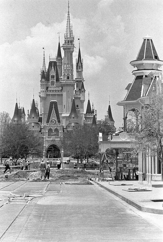 "Above: The Cinderella palace serves as a backdrop for workmen who prepare the proper concrete ""carpet"" at Walt Disney World, under construction near Orlando, Fla., July 7, 1971. Photo: Steve Starr, ASSOCIATED PRESS / AP1971"