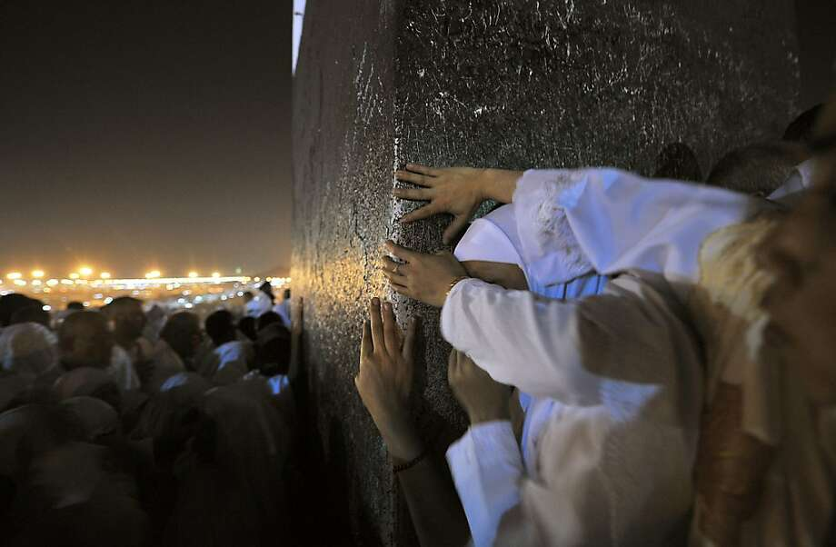 Muslim pilgrims touch a stoneon Mount Arafat, near the holy city of Mecca, ahead of the hajj main 