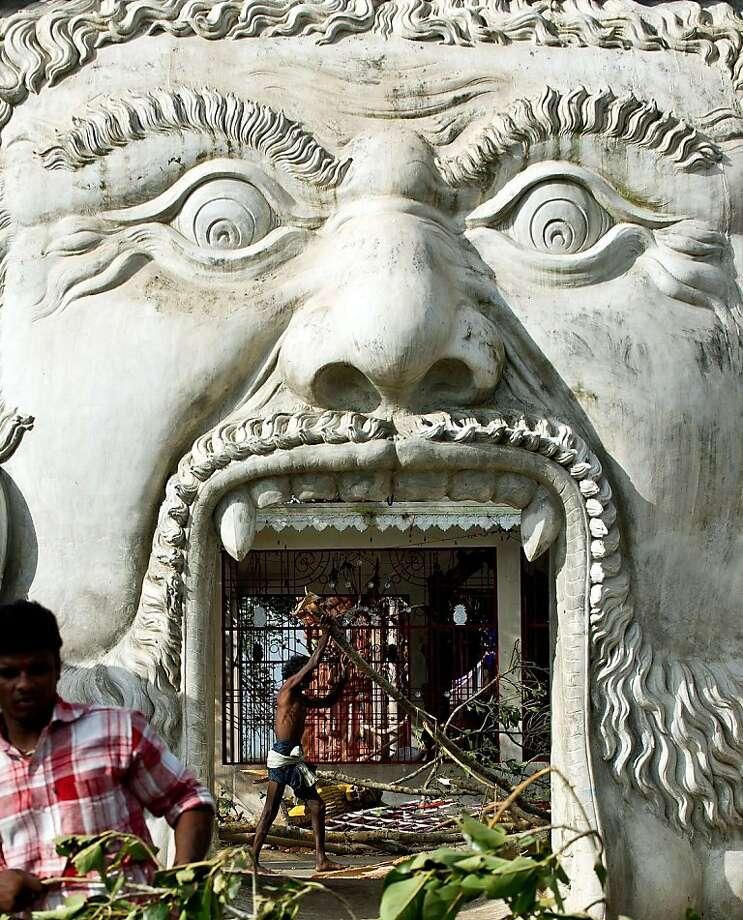 Toothpicks of the gods: Villagers remove branches from the goddess Kali temple at Gopalpur Junction, India, 