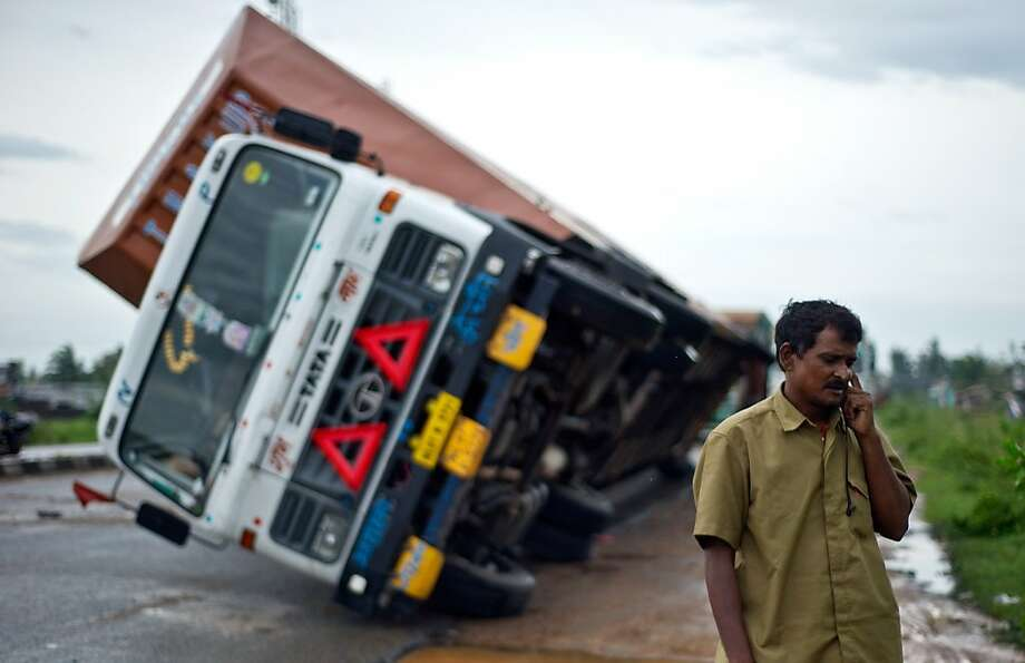 I might be a little late ... Indian truck driver Jairam Yadav   makes a call after his semi rig, laden with Toyotas, was toppled by Cyclone Phailin's winds on the   National Highway near Gopalpur, India. Photo: Manan Vatsyayana, AFP/Getty Images