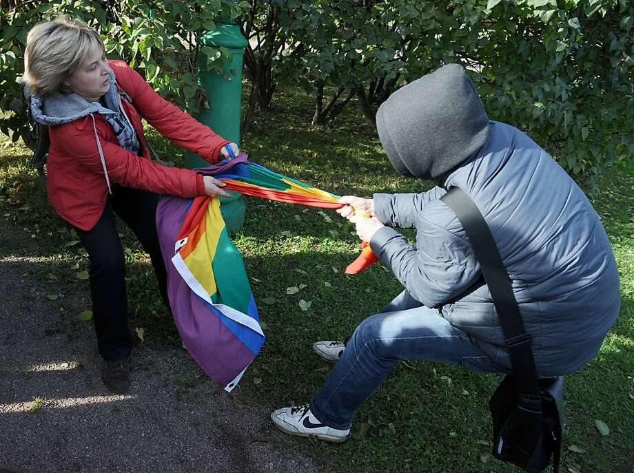 Rainbow theft in progress: A gay rights supporter tries to keep an anti-gay bully from stealing her flag during a pride event 