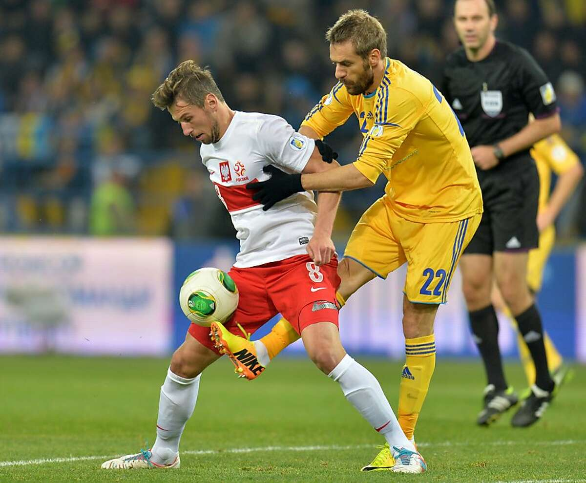 About to be an octave higher on the pitch: Grzegorz Wojtkowiak can only hope that Marko Devic's aim is true during the Fifa 2014 World Cup qualifier between Ukraine and Poland.