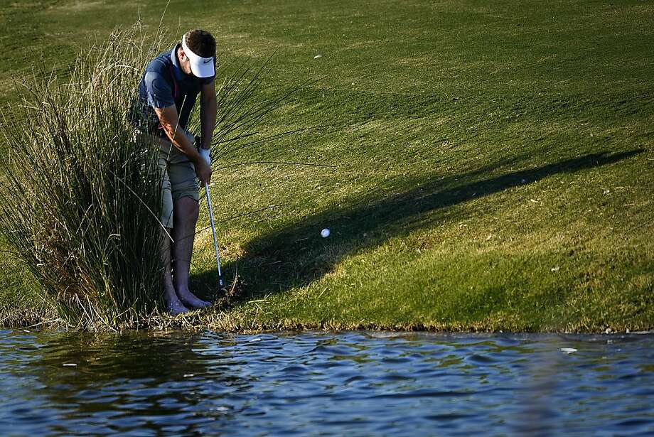 Weed whacker: Scottish golfer Scott Jamieson plays a difficult lie barefooted from the lake bank on the 14th hole 