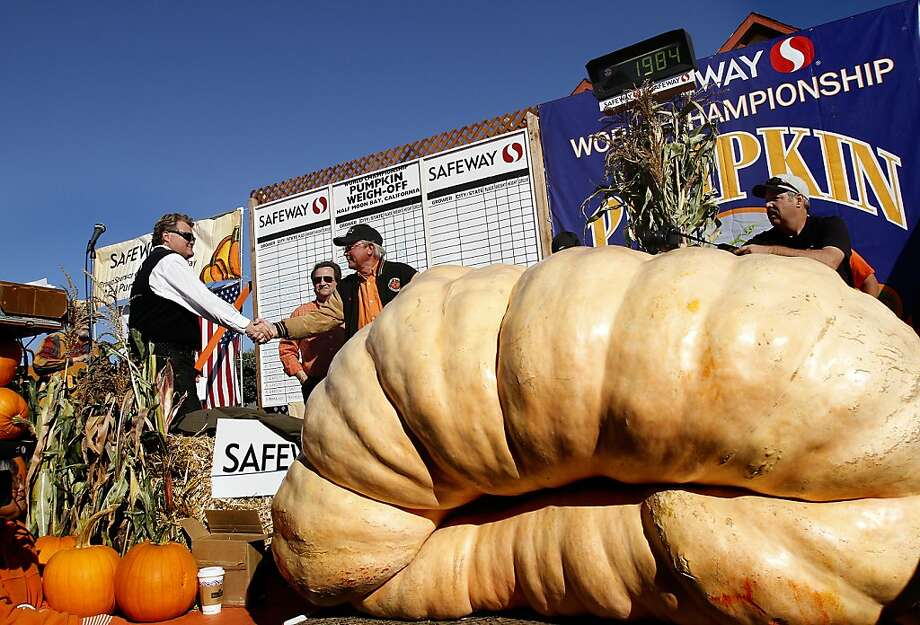 Gary Miller, center, is congratulated for his winning 1,985 pound pumpkin at the 40th Annual Safeway World Championship Pumpkin Weigh-Off in Half Moon Bay, Calif., on Monday, October 14, 2013.  Miller's pumpkin was not large enough to break the world record, but it was big enough to win the weight contest for the day.  The pumpkin will be on display at the Half Moon Bay Art and Pumpkin Festival this weekend. Photo: Sarah Rice, Special To The Chronicle