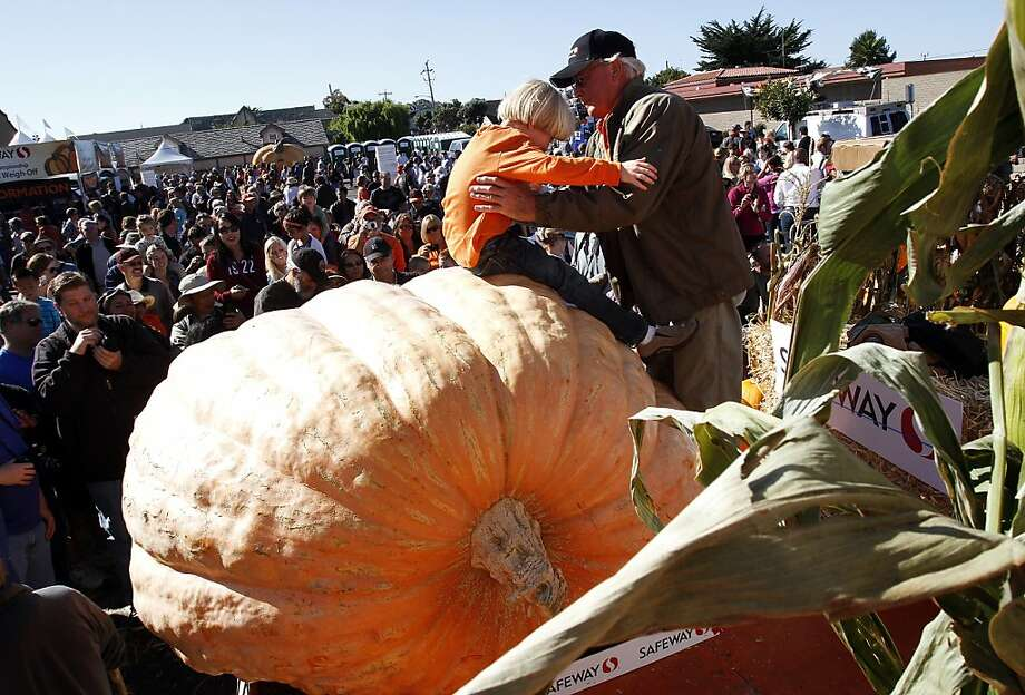 Gary Miller takes his grandson Benjamin Miller, 6, off his winning 1,985 pound pumpkin at the 40th Annual Safeway World Championship Pumpkin Weigh-Off in Half Moon Bay, Calif., on Monday, October 14, 2013.  Miller's pumpkin was not large enough to break the world record, but it was big enough to win the weight contest for the day. Photo: Sarah Rice, Special To The Chronicle