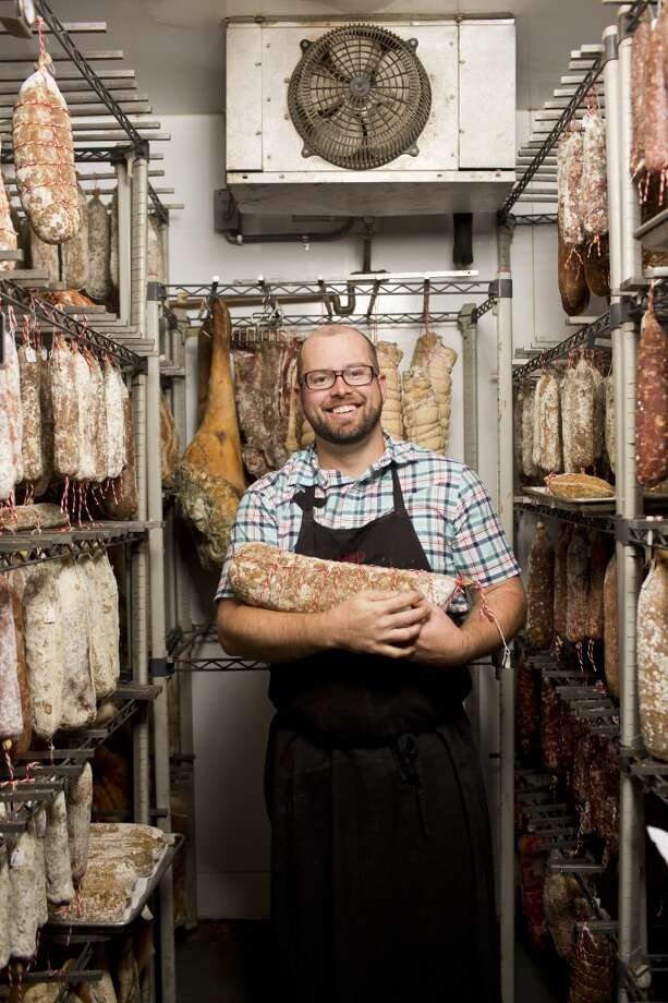 Ryan Harris of Fatted Calf cradles meat in the curing room. Photo: Jason Henry, Special To The Chronicle