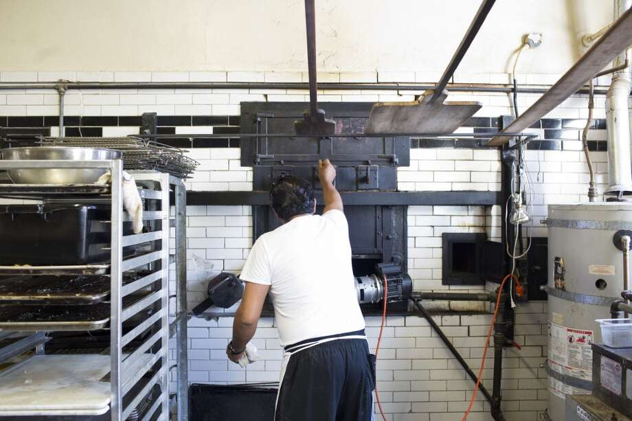 Model Bakery, an artisan bakery known for their buttery english muffins, fires their St. Helena based ovens with a gas powered blower, shooting flames into the century-old brick where they bake their goods in St. Helena. Photo: Jason Henry, Special To The Chronicle