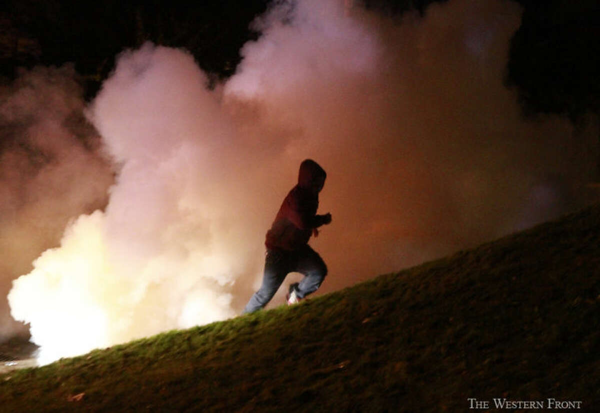 A man runs from a smoke bomb on Saturday, Oct. 12, 2013, at the corner of Indian and East Laurel Street in Bellingham, Wash. Police broke up a Bellingham Block Party. (Nick Gonzales, courtesy of The Western Front, special to seattlepi.com)