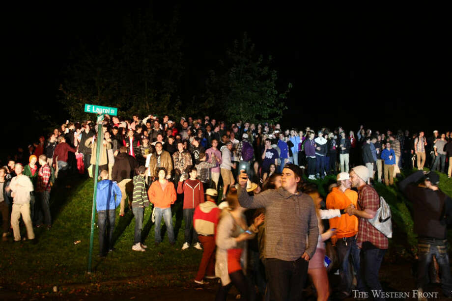 A man takes a cell phone picture as people huddle on a grass knoll at Laurel Park on Saturday, Oct. 12, 2013, in Bellingham, Wash. Bellingham Police sat in their idling cars as people threw beer bottles and other objects at them. (Jake Parrish, courtesy of The Western Front, special to seattlepi.com) / SEATTLEPI.COM