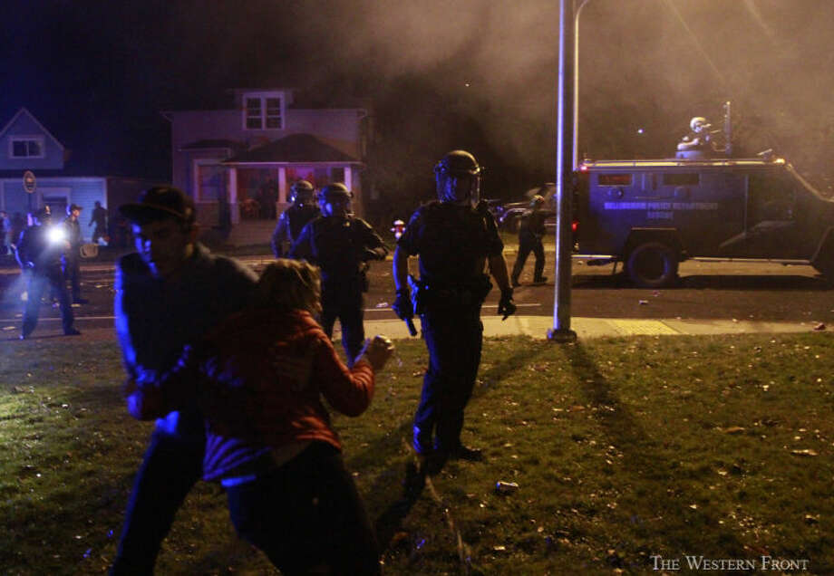 A man drags a woman away as police tell people to leave Indian Street near Laurel Park on Saturday Night, Oct. 12, in Bellingham, Wash. Bellingham Police Department rescue unit showed up after people were throwing beer bottles and other objects at idling police cars. (Nick Gonzales, courtesy of The Western Front, special to seattlepi.com) / SEATTLEPI.COM