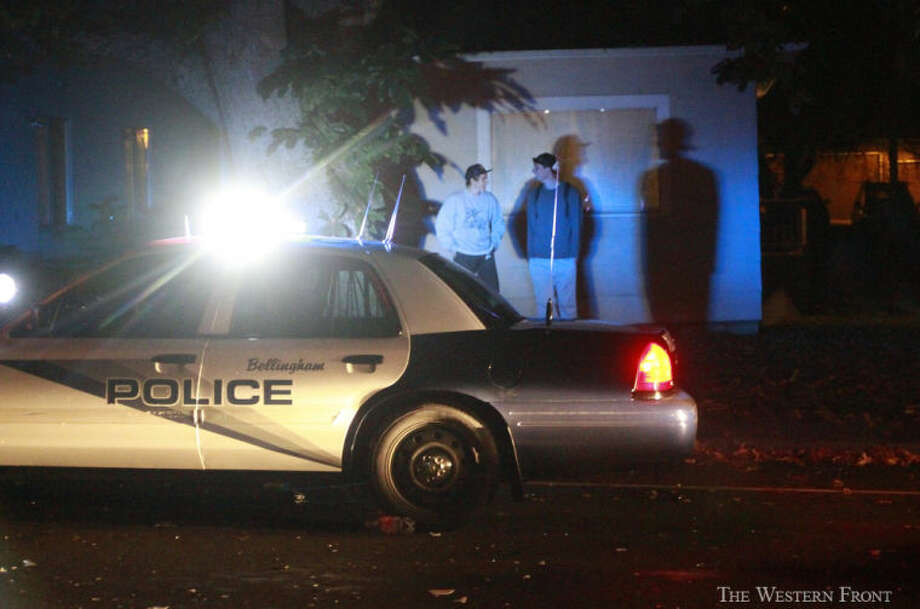 Two men talk and watch Bellingham Police clear Indian Street on Saturday, Oct. 12, 2013, in Bellingham, Wash. Bellingham Police Department rescue unit showed up after people were throwing beer bottles and other objects at idling police cars on Indian Street near Laurel Park. (Nick Gonzales, courtesy of The Western Front, special to seattlepi.com) / SEATTLEPI.COM