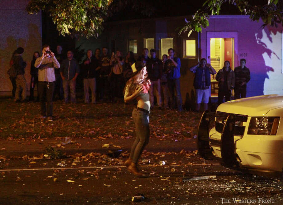 A woman displays herself to a Bellingham Police officer as onlookers watch on Saturday, Oct. 12, 2013, near Laurel Park in Bellingham, Wash. Bellingham Police Department rescue unit showed up after people were throwing beer bottles and other objects at idling police cars on Indian Street near Laurel Park. (Nick Gonzales, courtesy of The Western Front, special to seattlepi.com) / SEATTLEPI.COM