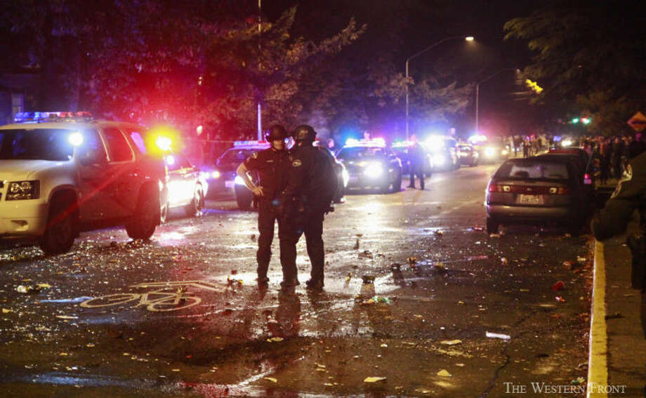 Two officers talk in the middle of the street on Saturday, Oct. 12, 2013, near Laurel Park in Bellingham, Wash. Bellingham Police Department rescue unit showed up after people were throwing beer bottles and other objects at idling police cars on Indian Street near Laurel Park. (Nick Gonzales, courtesy of The Western Front, special to seattlepi.com) / SEATTLEPI.COM
