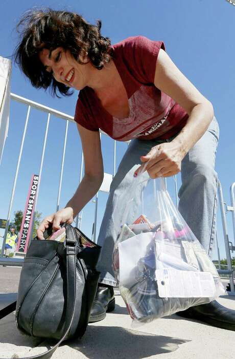 An Arizona Cardinals fan moves her purse contents into an NFL-approved clear bag. Photo: Ross D. Franklin / Associated Press