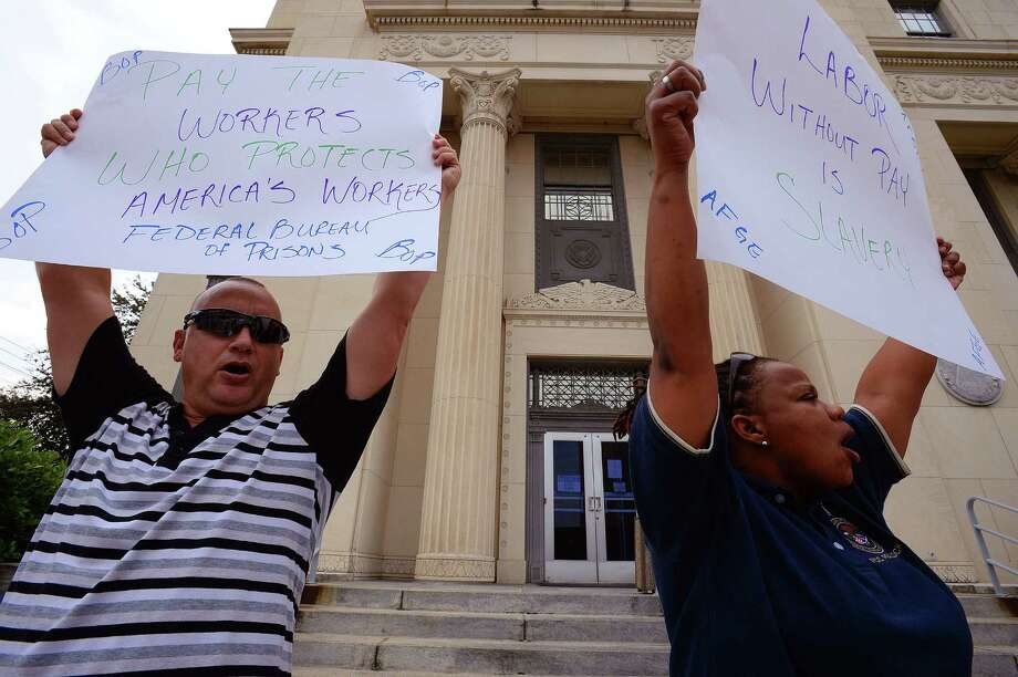 Federal employees Keith LaBier and Donna Hughley hold signs and chant about the government shut down during a protest at the Jack Brook's Federal Courthouse on Monday. Around 1,000 local workers are out of work or working with out pay due to the shutdown.  Photo taken Monday, October 14, 2014 Guiseppe Barranco/The Enterprise Photo: Guiseppe Barranco, Photo Editor
