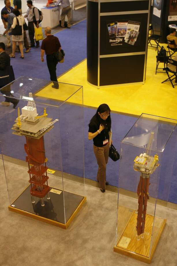 Baozhi Zhu, a design engineer with GE Oil & gas business Vetcogray, looks at models of a closed Centerwell truss spar (left) and a model of a cell spar at the Technip exhibit at the 2008 Offshore Technology Conference in Houston. Photo: Steve Campbell, Houston Chronicle