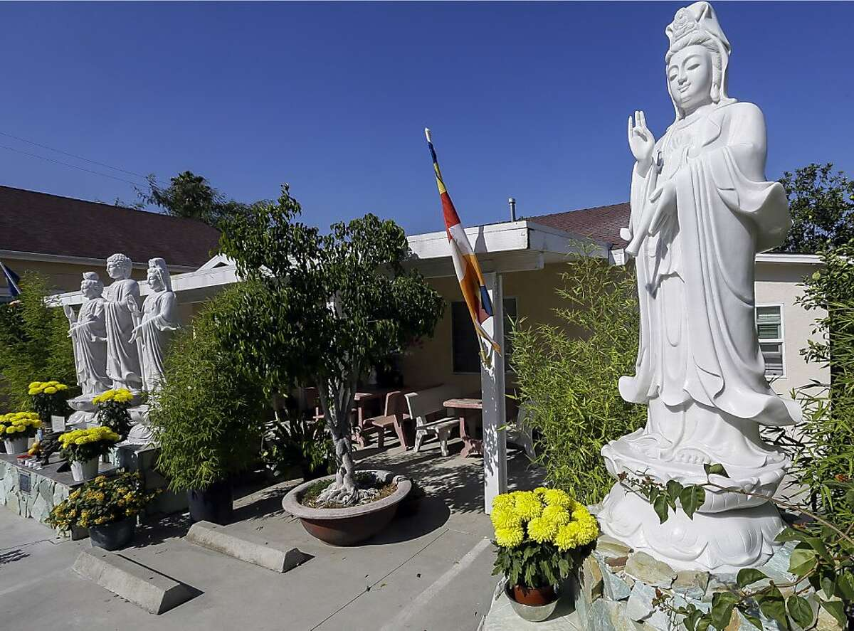 In this Sept. 18, 2013, photo, Buddhist statues decorate the entrance to the Lu Mountain Temple in Rosemead, Calif. The temple has become a repository for the colorful crystals and a tooth and a hair that are believed to have come from the body of the Buddha himself. (AP Photo/Damian Dovarganes)