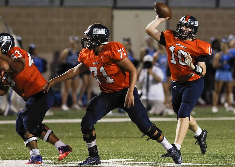 Brandeis quarterback Brian Chapman (right) throws a pass behind the blocking of Arturo Flores (left) and Gabriel Cisneros during the second quarter of  their game with Johnson at Farris Stadium on Saturday, Sept. 7, 2013. Photo: Marvin Pfeiffer, San Antonio Express-News