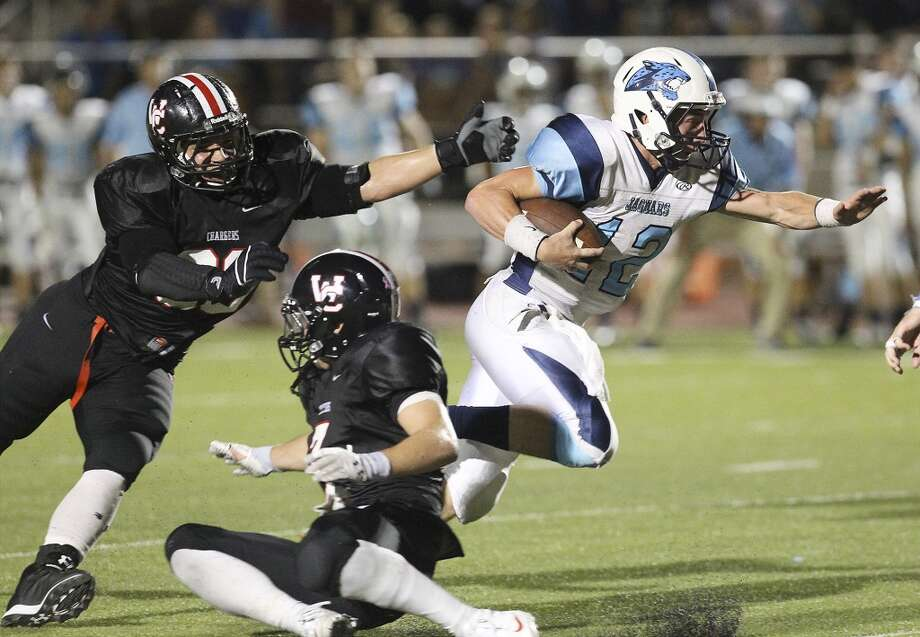 Johnson Jaguars quarterback Hunter Rittimann (12) slips a tackle from Churchill Chargers' Jonah Kucinski-Stewart (90) as he heads for a touchdown at Heroes Stadium on Friday, Oct. 11, 2013. Photo: Kin Man Hui, San Antonio Express-News