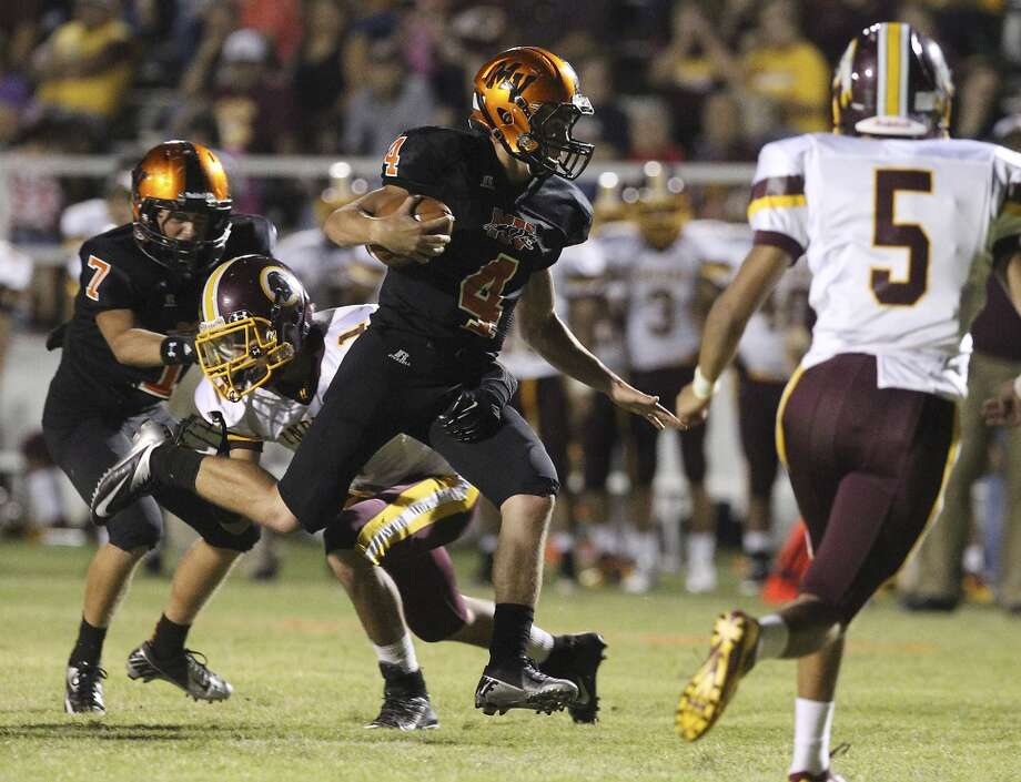 Medina Valley's Bradley Griggs (04) runs between Harlandales' Ramzey Martinez (01) and Ruben Zavala (05) during their game at Panther Stadium in Castroville on Friday, Sept. 27, 2013. Photo: Kin Man Hui, San Antonio Express-News