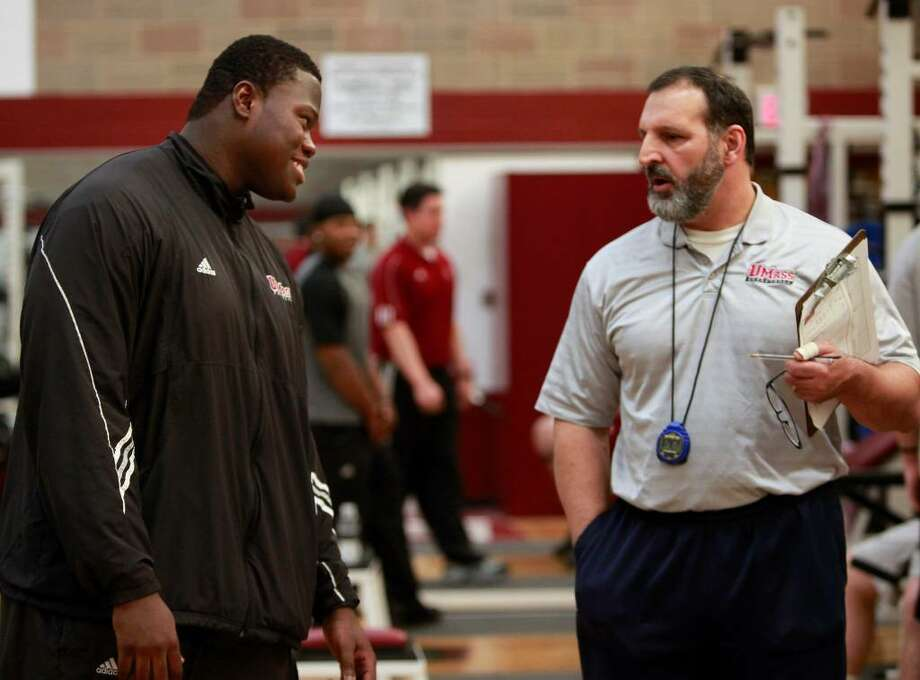 University of Massachusetts offensive tackle Vladimir Ducasse, left, originally from Haiti, speaks with strength and conditioning coach Bob Otrando, right, in a gym on the school's campus, in Amherst, Mass., on Friday, Jan. 22, 2010. Ducasse, who has lived in the United States since he was 14, is headed to the Senior Bowl college all-star football game with thoughts of impressing pro scouts, and concerns about his native Haiti. (AP Photo/Steven Senne) Photo: Steven Senne, AP / AP