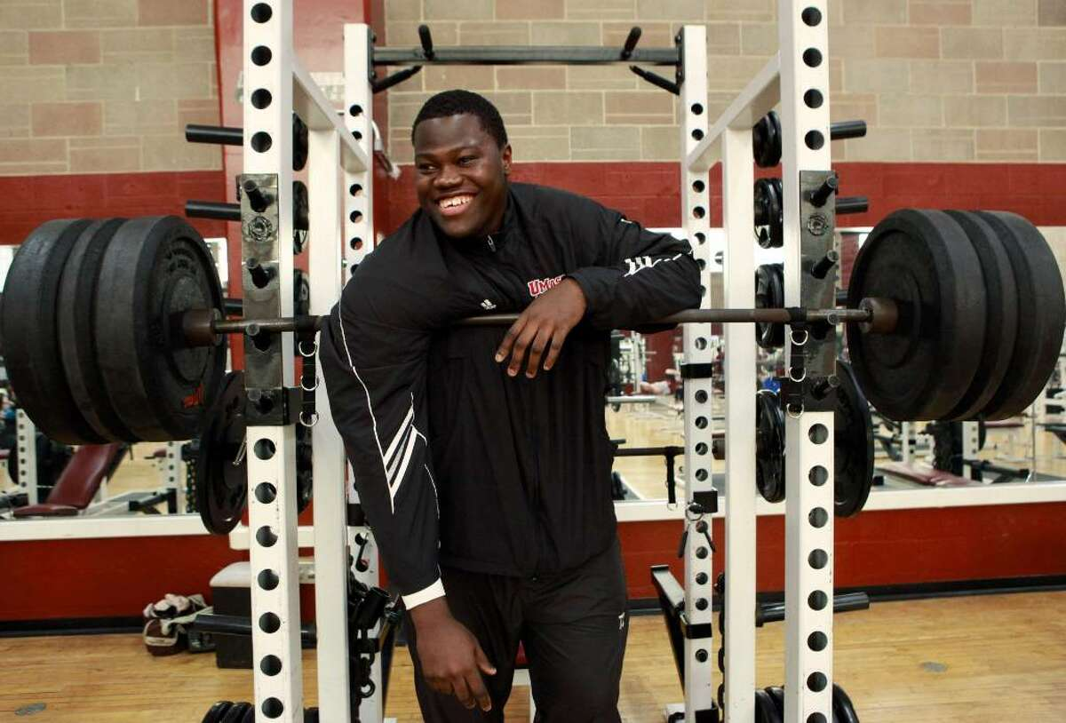 University of Massachusetts offensive tackle Vladimir Ducasse, originally from Haiti, smiles while having his photo taken in a gym on the school's campus, in Amherst, Mass., on Friday, Jan. 22, 2010. Ducasse, who has lived in the United States since he was 14, is headed to the Senior Bowl college all-star football game with thoughts of impressing pro scouts, and concerns about his native Haiti. (AP Photo/Steven Senne)