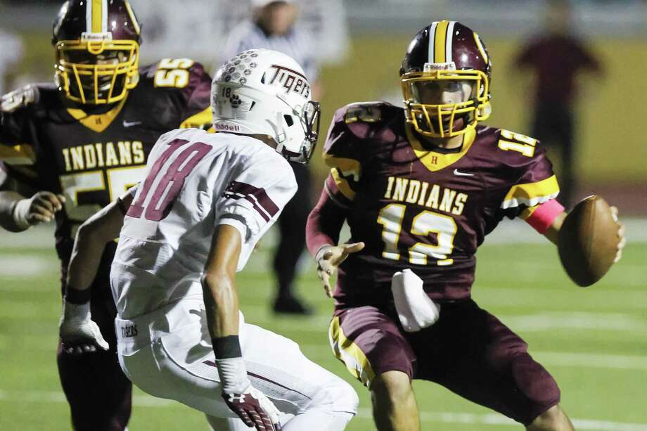 Harlandale quarter back Brandon Ramon, right, fakes a pitch to his left on Floresville's Bradley Bunn before scoring a second quarter touchdown during their game at Harlandale Memorial Stadium on Oct. 4. Photo: Marvin Pfeiffer/ Express-News