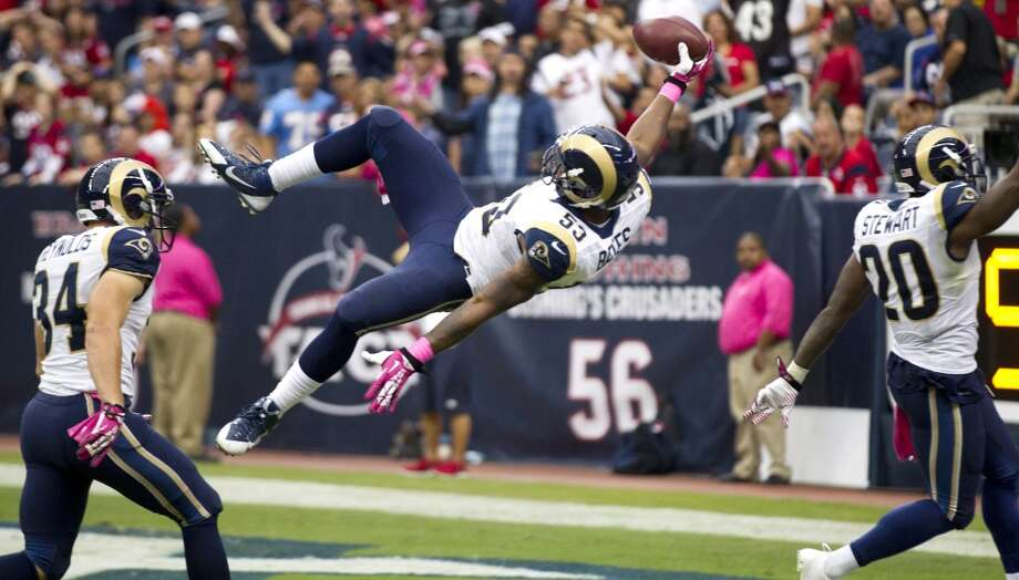 Rams linebacker Daren Bates (53) leaps into the end zone as he returns a fumble by Texans kick returner Keshawn Martin for a touchdown. Photo: Brett Coomer, Houston Chronicle
