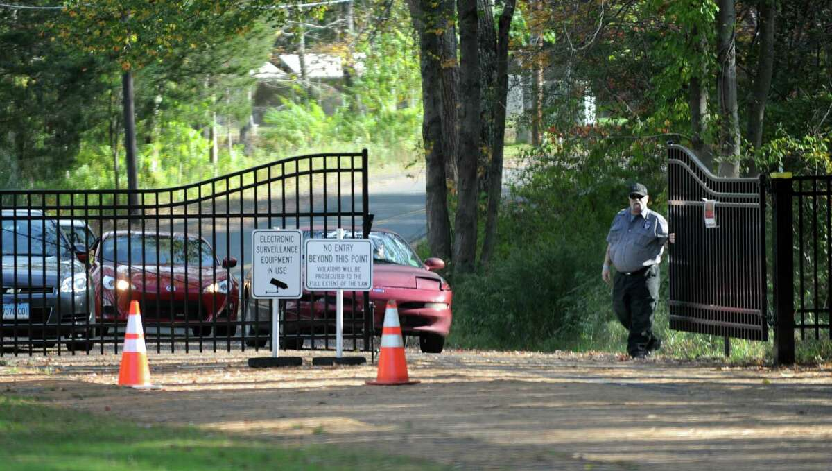 A security guard opens the gate to the old Sandy Hook Elementary School Monday, Oct. 14, 2013, to allow cars to leave the site. A construction company is getting ready to demolish the school building next week.