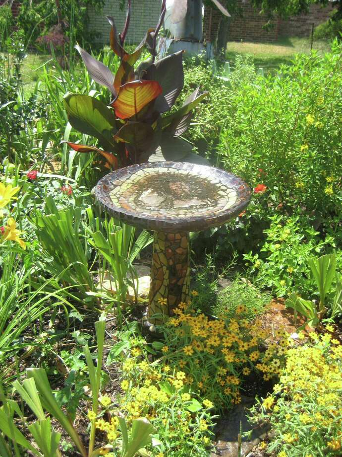 Bird baths can be plain and functional or be incorporated into the garden as works of art. Photo: Houston Chronicle