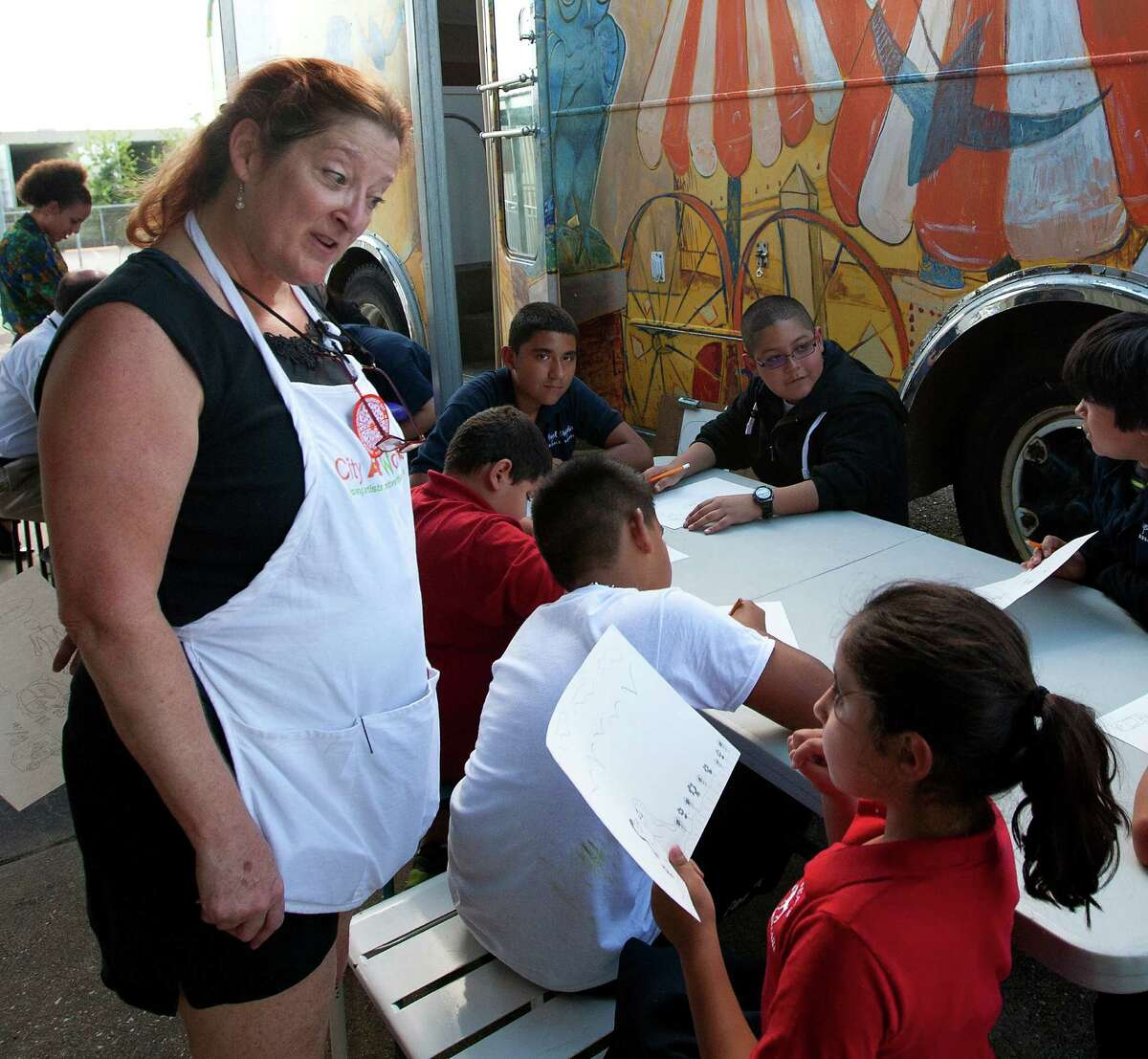 Art Instructor Susan Wingfield, left, talks to Natalie Villareal, 8, outside the Orange Show Art Bus as she teaches art at Cage Elementary, Wednesday, Oct. 9, 2013, in Houston. A grant allowed the funding to convert a 1964 bus into a rolling classroom meant to offer art programs at schools where such have been curtailed or don't exist.