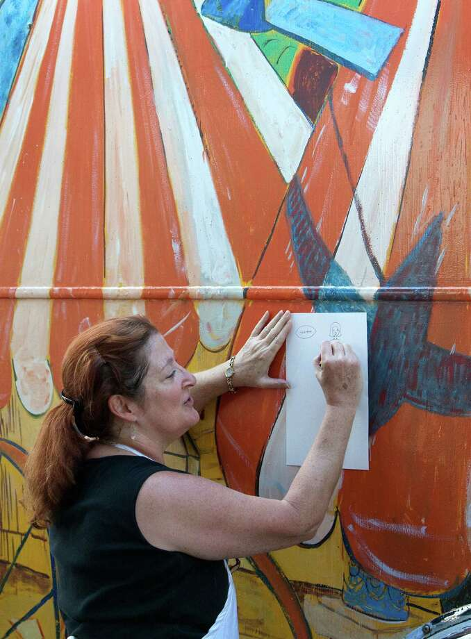 Art Instructor Susan Wingfield, center, stands outside the Orange Show Art Bus as she teaches students art at Cage Elementary, Wednesday, Oct. 9, 2013, in Houston. A grant allowed the funding to convert a 1964 bus into a rolling classroom meant to offer art programs at schools where such have been curtailed or don't exist. Photo: Cody Duty, Houston Chronicle / © 2013 Houston Chronicle